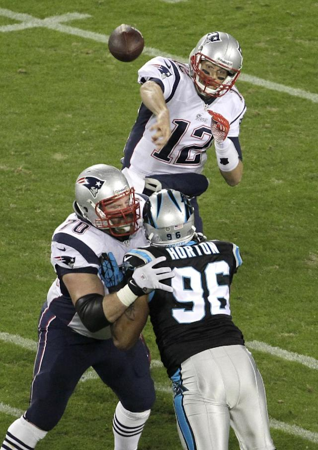 New England Patriots' Tom Brady (12) throws a pass under pressure from Carolina Panthers' Wes Horton (96) during the first half of an NFL football game in Charlotte, N.C., Monday, Nov. 18, 2013. (AP Photo/Bob Leverone)