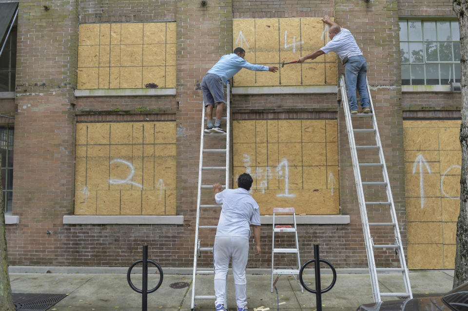 A crew covers windows along Julia St. in the Central Business District as Hurricane Ida approaches the Louisiana coast in New Orleans, La. Saturday, Aug. 28, 2021. Residents across Louisiana's coast rushed to prepare for the approach of an intensifying Hurricane Ida. The storm is expected to bring winds as high as 140 mph when it slams ashore late Sunday.( Max Becherer, NOLA.com, The Times-Picayune/The New Orleans Advocate via AP)