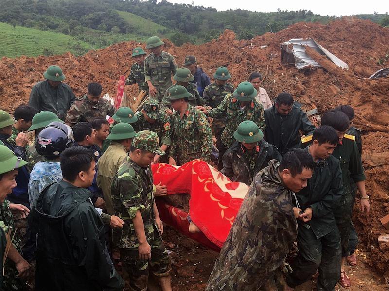 Military personnel carrying a body recovered from the site of a landslide in central Vietnam's Quang Tri province (Vietnam News Agency/AFP via Gett)