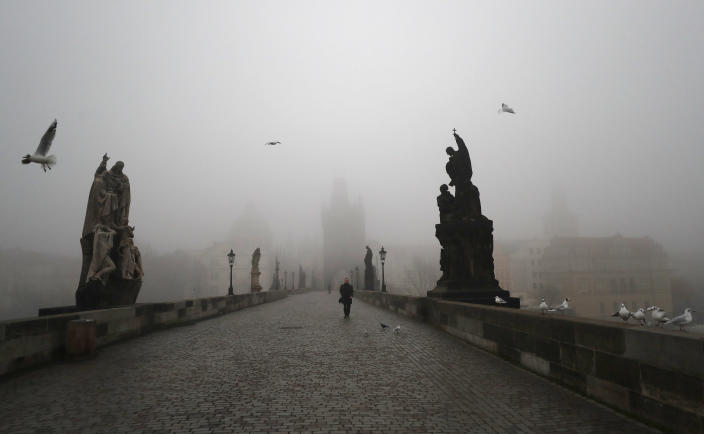 FILE - In this Wednesday, Feb. 24, 2021 file photo, a man walks across the medieval Charles Bridge in Prague, Czech Republic. Europe recorded 1 million new COVID-19 cases last week, an increase of 9% from the previous week and ending a six-week decline, WHO said Thursday, March 4, 2021. The so-called UK variant is of greatest concern in the 53 countries monitored by WHO in Europe. (AP Photo/Petr David Josek, File)
