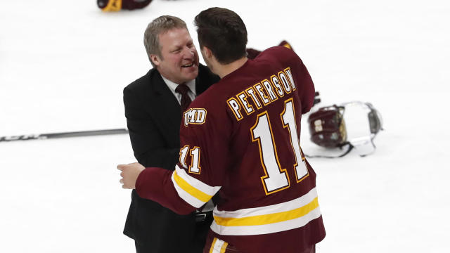 Head Coach Scott Sandelin and Avery Peterson of the Minnesota-Duluth Bulldogs celebrate their victory. (Photo by Carlos Gonzalez/NCAA Photos via Getty Images)