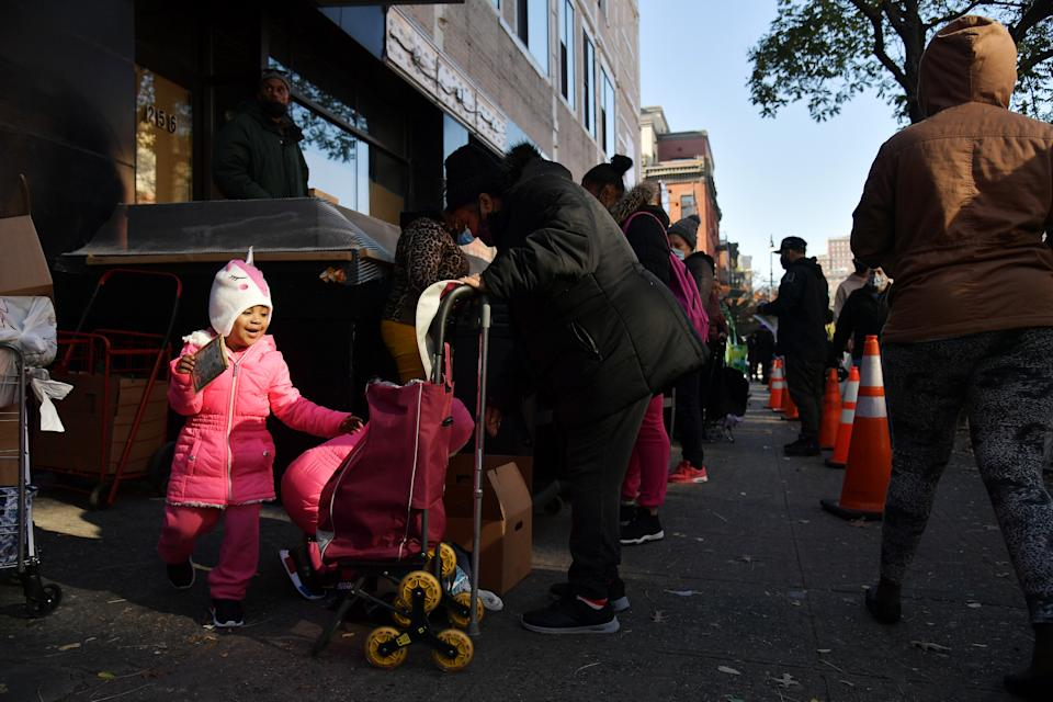 NEW YORK, NEW YORK - NOVEMBER 16: A view of a child as she stands in line with her family as Food Bank for New York City distributes turkeys and Thanksgiving fixings with support from Stop & Shop and WBLS' The Steve Harvey Morning Show on November 16, 2020 in New York City. (Photo by Michael Loccisano/Getty Images for Food Bank For New York City)