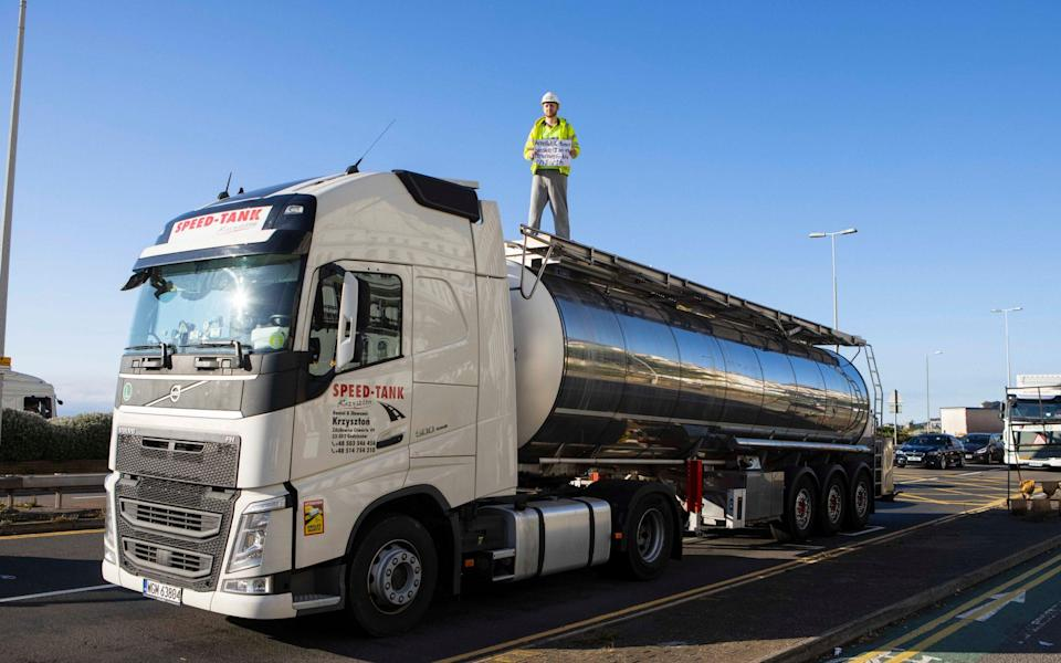 An Insulate Britain protester climbs on top of a tanker at Dover