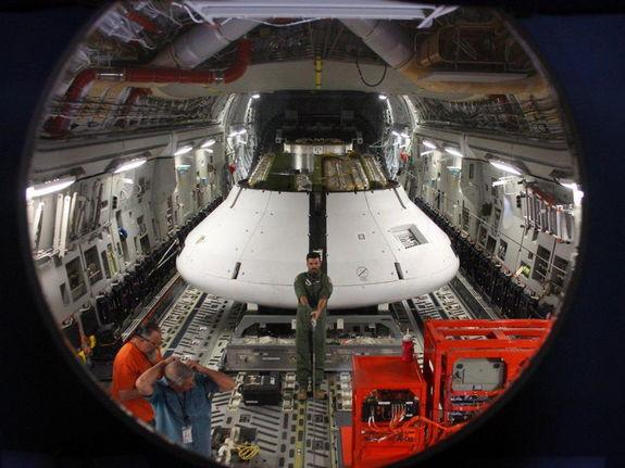 A model of NASA's Orion spacecraft is loaded into a C-17 airplane on May 1, 2013. The capsule was dropped from an altitude of 25,000 feet (7,620 meters) above the Arizona dessert to test its parachutes.