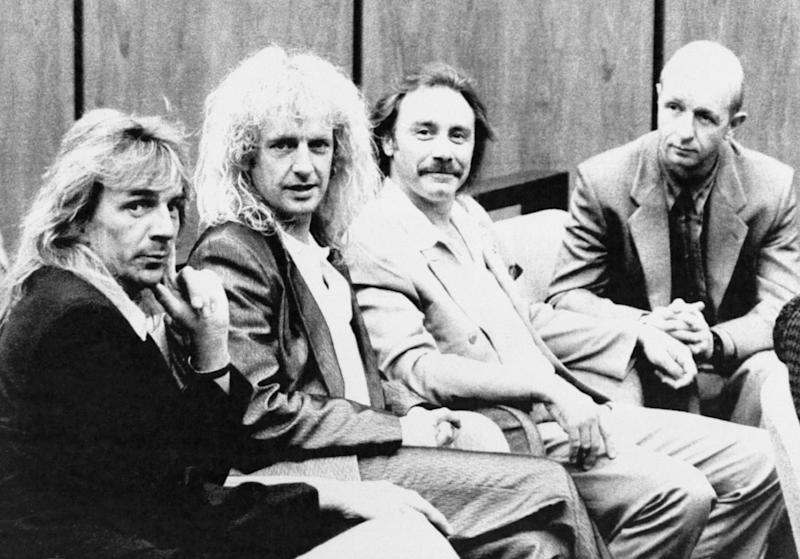 Judas Priest members Glenn Tipton, K.K. Downing, Ian Hill and Rob Halford sit together on courtroom bench.