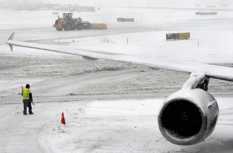 A snow plow clears the runway Monday, Feb. 3, 2014 at Newark Liberty International Airport in Newark, NJ. Air traffic is disrupted in Ohio, the Mid-Atlantic and the Northeast as another winter storm bears down on the eastern U.S., only a day after temperatures soared into the 50s. (AP Photo/Matt York)