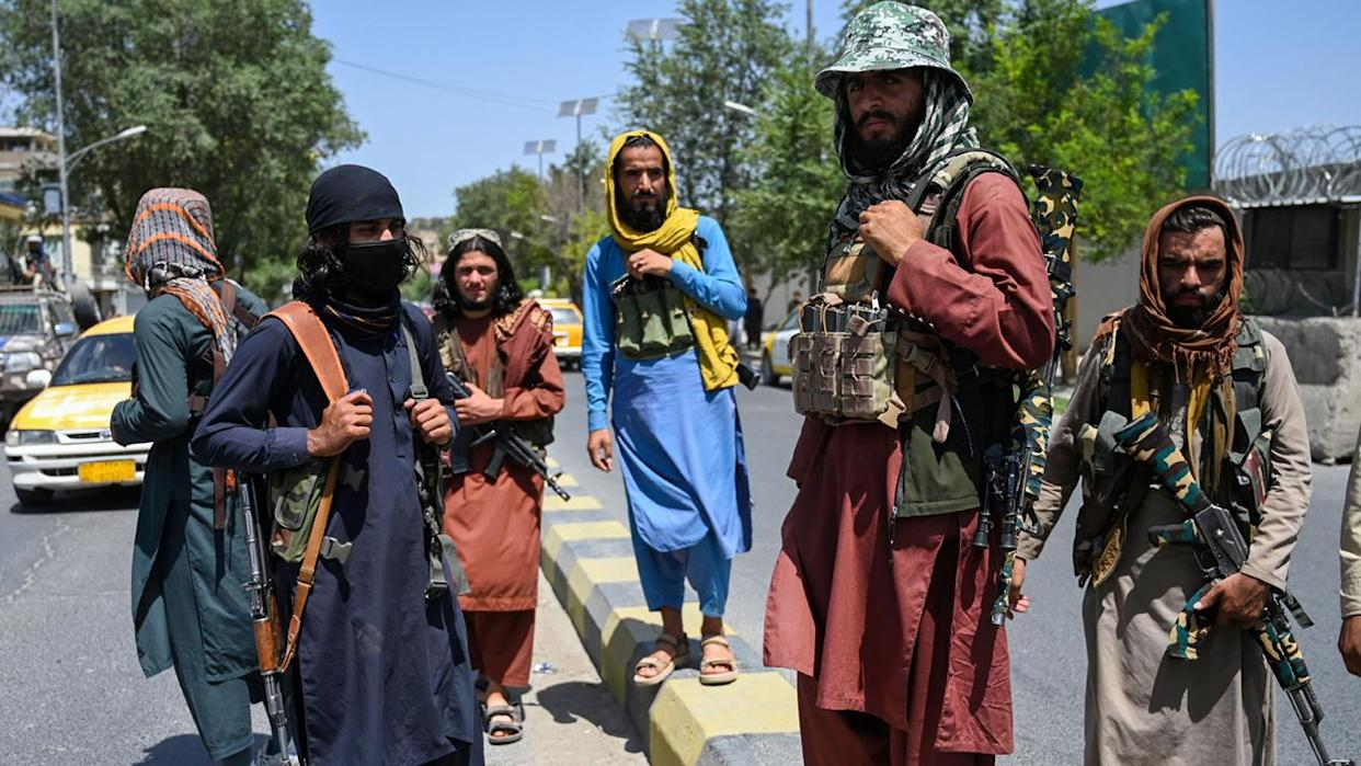 Taliban fighters stand guard along a street near the Zanbaq Square in Kabul on Monday.
