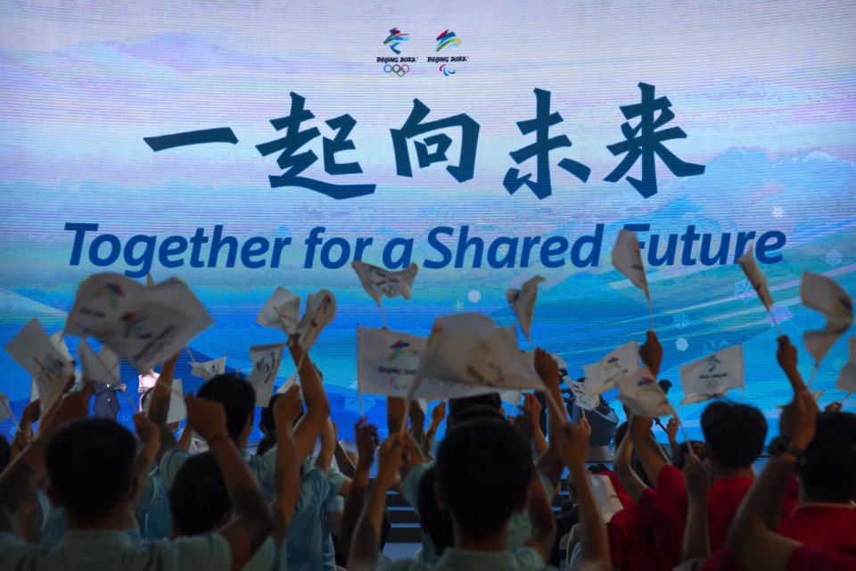 """Participants cheer as the motto for the 2022 Beijing Winter Olympics and Paralympics is revealed at a launch ceremony in Beijing, Friday, Sept. 17, 2021. Organizers on Friday announced """"Together for a Shared Future"""" as the motto of the next Olympics, which is scheduled to begin on Feb. 4 of next year. (AP Photo/Mark Schiefelbein)"""