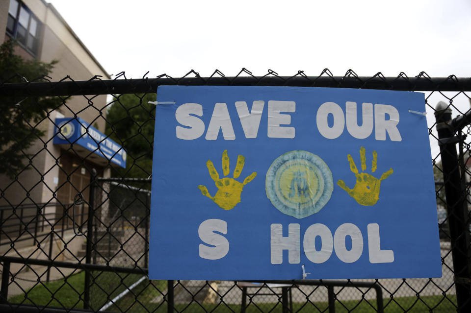 A sign made by parents and students of Queen of the Rosary Catholic Academy hangs on the fence outside the school in Brooklyn borough of New York, Tuesday, Aug. 4, 2020. Queen of the Rosary is one of six Catholic schools in Brooklyn and Queens that will permanently close at the end of August. Nationwide, more than 140 Catholic schools will not reopen in the fall. (AP Photo/Jessie Wardarski)