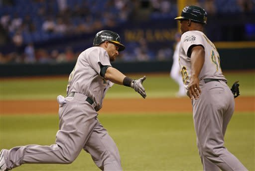 Oakland Athletics Jonny Gomes reaches his hand out to Tye Waller after hitting the game winning home run in the 12th inning against the Tampa Bay Rays of a baseball game, Saturday, May 5, 2012, in St. Petersburg, Fla. (AP Photo/Scott Iskowitz)