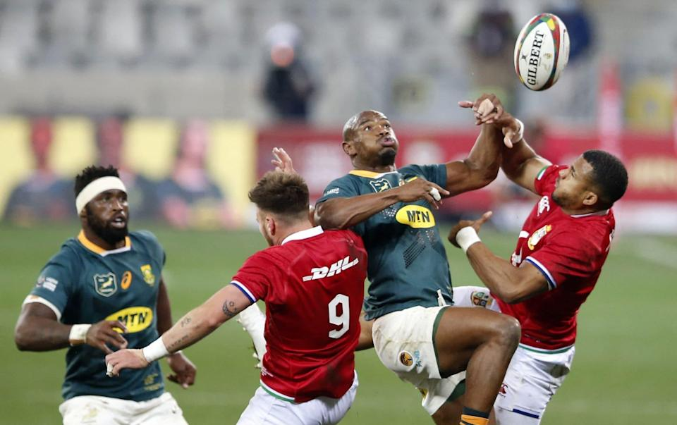 South Africa's left wing Makazole Mapimpi (2R) leaps for the ball with British and Irish Lions' scrum-half Ali Price (C) and British and Irish Lions' wing Anthony Watson (R) as South Africa's blindside flanker Siya Kolisi (L) looks on during the first rugby union Test match between South Africa and the British and Irish Lions at The Cape Town Stadium in Cape Town on July 24, 2021. - GETTY IMAGES