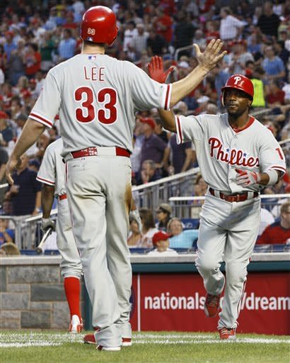 Philadelphia Phillies' Jimmy Rollins (11) celebrates with Cliff Lee (33) after Rollins hit a two-run home run in the fourth inning of a baseball game against the Washington Nationals, Tuesday, July 31, 2012, in Washington. (AP Photo/Carolyn Kaster)