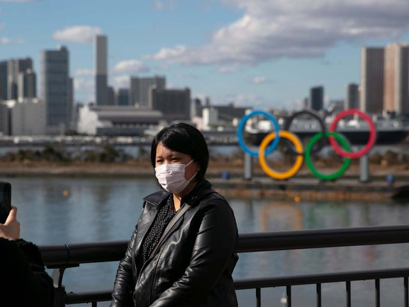 A tourist poses in front of the Olympic rings in Tokyo wearing a face mask amid the coronavirus outbreak: AP