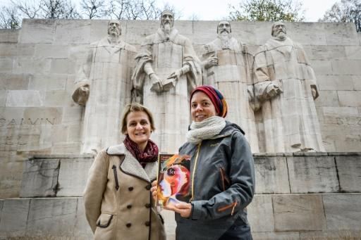 "Geneva theology professors Elisabeth Parmentier (L) and Lauriane Savoy pose under the Reformation Wall with a copy of ""A Women's Bible"""