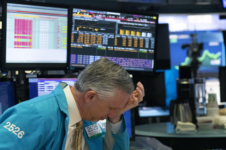 FILE - In this Wednesday, March 18, 2020 file photo, a trader holds his hand to his head after trading was halted at the New York Stock Exchange in New York. On March 23, 2020, the S&P 500 fell 2.9%. In all, the index dropped nearly 34% in about a month, wiping out three years' worth of gains for the market. (AP Photo/Mark Lennihan)