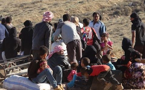 Syrians wait at the border areas near Jordan after they fled from the ongoing military operations by Bashar al-Assad regime  - Credit: Ammar Al Ali /Anadolu Agency/Getty Images