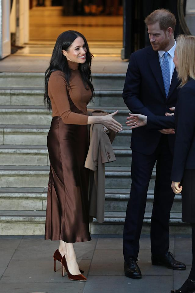 Meghan wore a trendy satin midi skirt for her first engagement of 2020. [Photo: Getty]