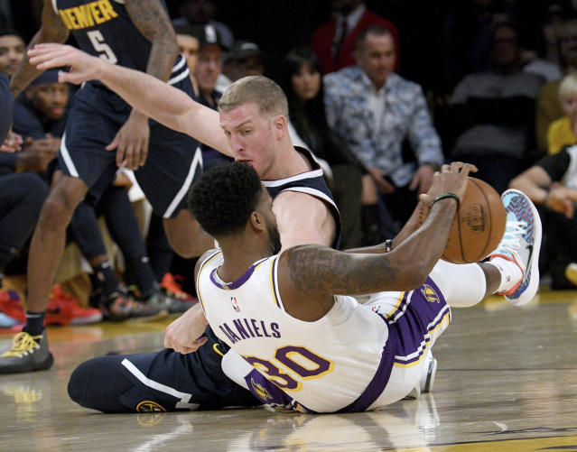 Los Angeles Lakers guard Troy Daniels, front and Denver Nuggets center Mason Plumlee hit the floor for a loose ball during the second half of an NBA basketball game Sunday, Dec. 22, 2019, in Los Angeles. The Nuggets won 128-104. (AP Photo/Michael Owen Baker)