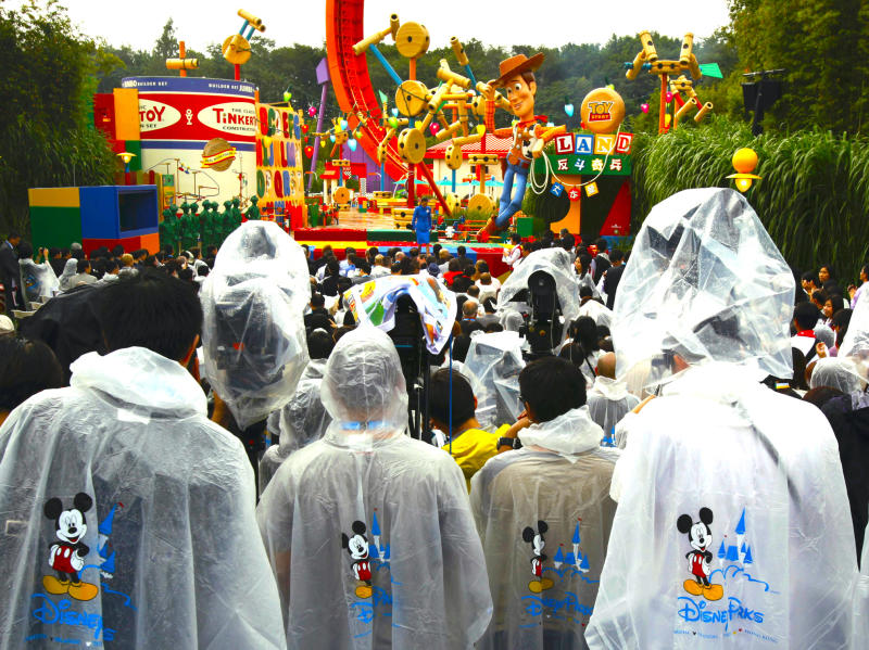 "Journalists wearing ponchos stand in the rain during the opening ceremony of Toy Story Land at Hong Kong Disneyland November 17, 2011. The new themed area, inspired by the global blockbuster ""Toy Story"" trilogy, is the first phase of the resort's expansion project. REUTERS/Bobby Yip (CHINA - Tags: TRAVEL SOCIETY BUSINESS MEDIA) - GF2E7BH0L7701"