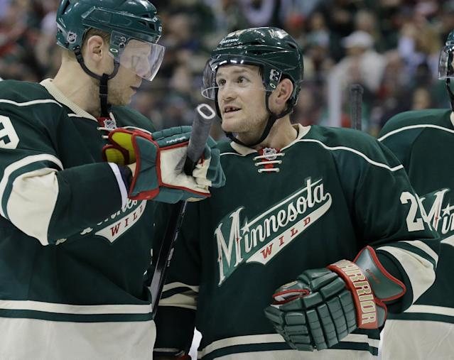 FILE - In this April 21, 2014 file photo, Minnesota Wild center Mikko Koivu (9), of Finland, left, and Minnesota Wild left wing Matt Cooke, right, talk before a face-off during the second period of Game 3 of an NHL hockey first-round playoff series against the Colorado Avalanche in St. Paul, Minn. The NHL cracked down hard on Matt Cooke, suspending the Minnesota Wild left wing for seven games Wednesday, April 23, 2014, for his knee-to-knee hit that injured Colorado Avalanche defenseman Tyson Barrie. (AP Photo/Ann Heisenfelt, File)
