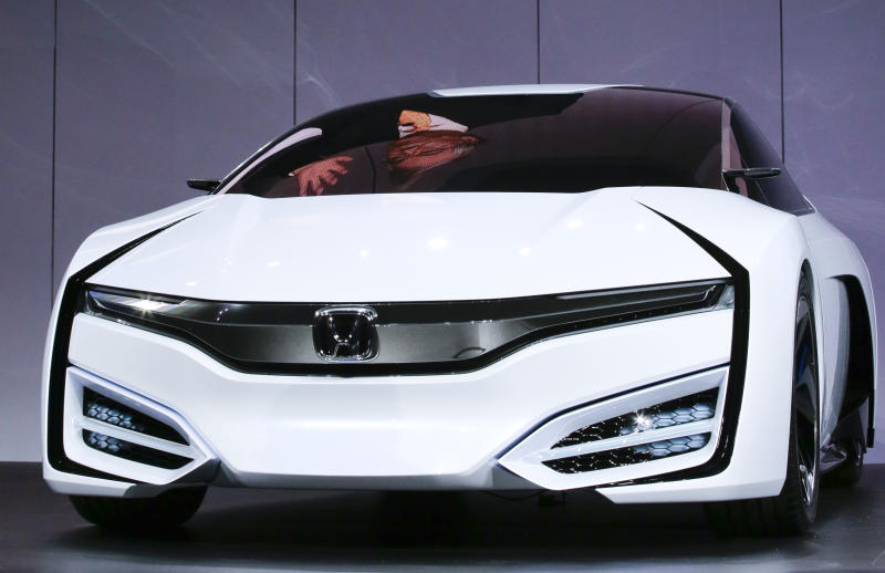 Tetsuo Iwamura, president and chief executive officer of American Honda Motor Co., Inc., is reflected in a window as he talks about the Honda FCEV Concept during it's debuted at the Los Angeles Auto Show in Los Angeles, Wednesday, Nov. 20, 2013. (AP Photo/Chris Carlson)