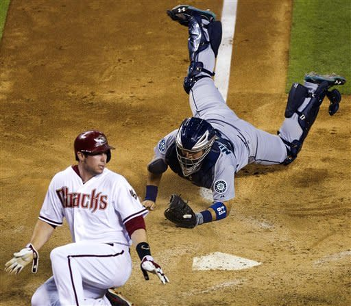Arizona Diamondbacks' Paul Goldschmidt scores ahead of the tag by Seattle Mariners catcher Jesus Montero during the sixth inning of an interleague baseball game, Monday, June 18, 2012, in Phoenix. (AP Photo/The Arizona Republic, Michael Chow) MARICOPA COUNTY OUT; MAGS OUT; NO SALES