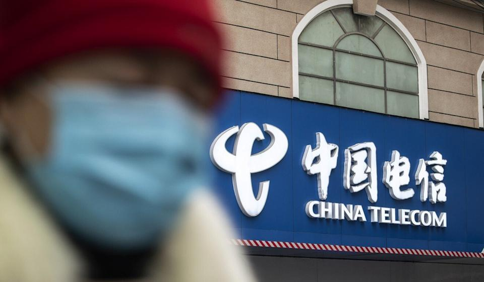 A pedestrian walks past a China Telecom store in Shanghai, China last week. Photo: Bloomberg