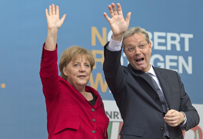 File - In this May 9, 2012 file picture German Chancellor Angela Merkel, left, waves to the crowd as she attends an election campaign rally together with Norbert Roettgen, right, top candidate of the Christian Democratic Union party CDU for the North Rhine-Westphalia federal state elections in Gelsenkirchen, Germany. Germany's most populous state holds an election Sunday May 13, 2012 , with polls pointing to likely re-election for a center-left regional government that Chancellor Angela Merkel has sought to label as irresponsibly spendthrift. About 13.2 million people are eligible to vote for the state legislature in North Rhine-Westphalia in western Germany, which includes Cologne, Duesseldorf and the industrial Ruhr region. (AP Photo/Martin Meissner,File)