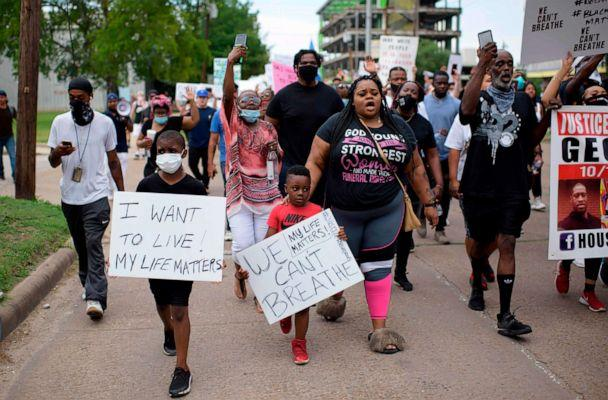 PHOTO: People hold signs as they protest and mourn the death of George Floyd in Houston, May 30, 2020. (Mark Felix/AFP via Getty Images)