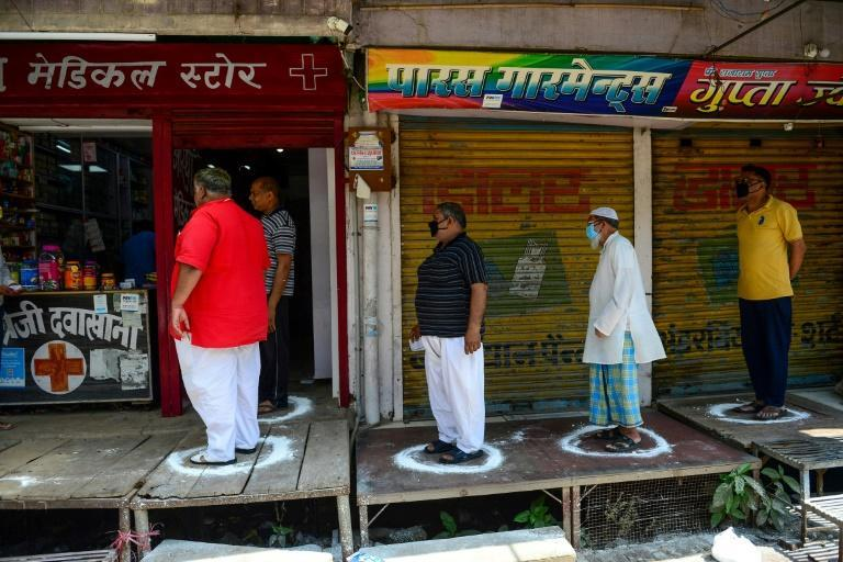 People stand on designated areas to maintain social distancing as they queue outside a medical store in Allahabad, India