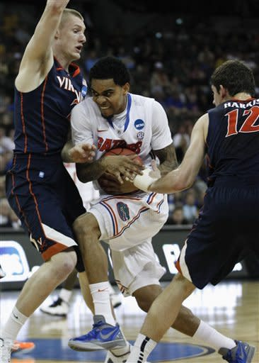 Florida's Mike Rosario is sandwiched between Virginia's Paul Jesperson, left, and Joe Harris, in the first half of an NCAA tournament second-round college basketball game at CenturyLink Center in Omaha, Neb., Friday, March 16, 2012. (AP Photo/Orlin Wagner)