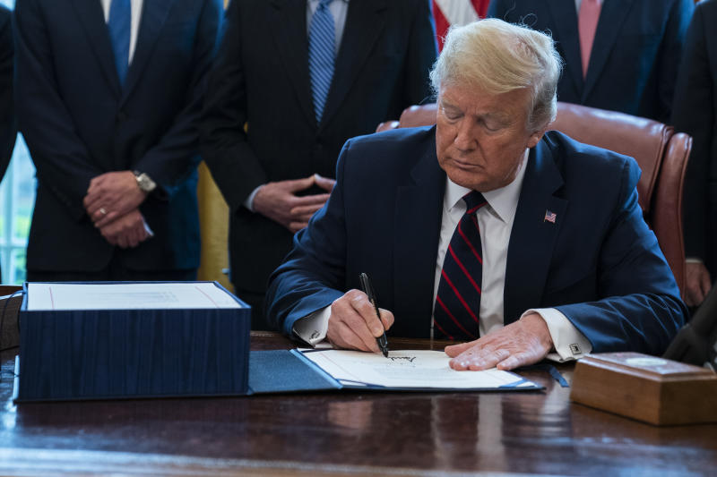 President Donald Trump signs the coronavirus stimulus relief package in the Oval Office at the White House, Friday, March 27, 2020, in Washington. (AP Photo/Evan Vucci)
