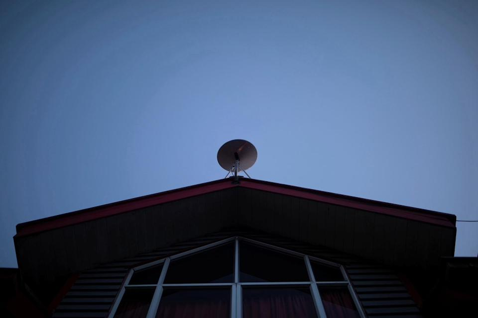 The Starlink antenna is seen on the roof of the John F Kennedy School located in the village of Sotomo, outside the town of Cochamo, Los Lagos region, Chile, August 7, 2021. Picture taken August 7, 2021. Sotomo is one of two places in Chile to be chosen for a pilot project run by billionaire Elon Musk to receive free internet for a year. The signal is received via a satellite dish installed on the school's roof, which transmits through a Wi-Fi device. REUTERS/Pablo Sanhueza         SEARCH