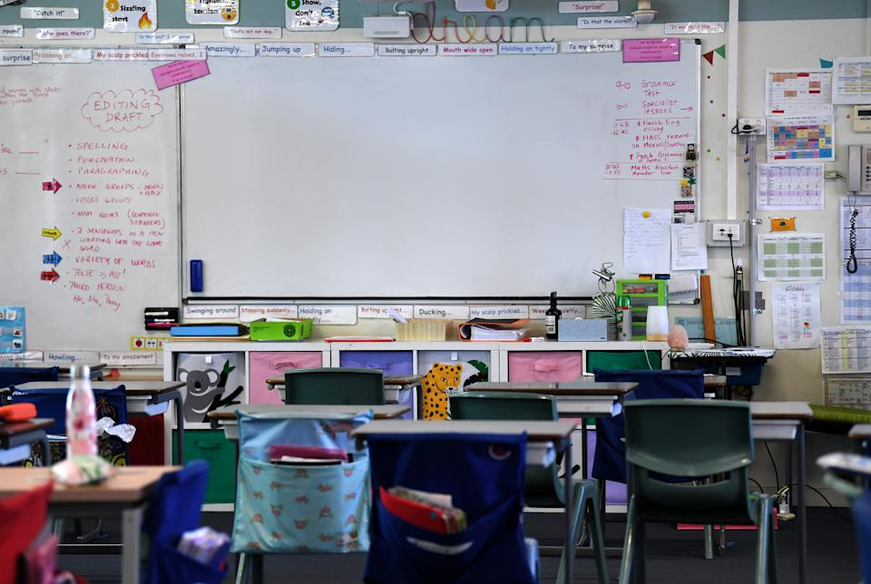 Pictured is an empty classroom with a whiteboard.
