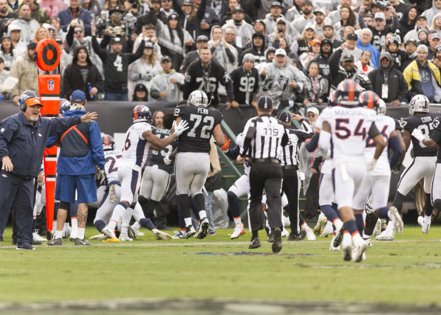 <p>Oakland Raiders wide receiver Michael Crabtree (15) and Denver Broncos cornerback Aqib Talib (21) fight on the sidelines as both teams run to the fight during the first quarter at Oakland Coliseum. Mandatory Credit: Neville E. Guard-USA TODAY Sports </p>