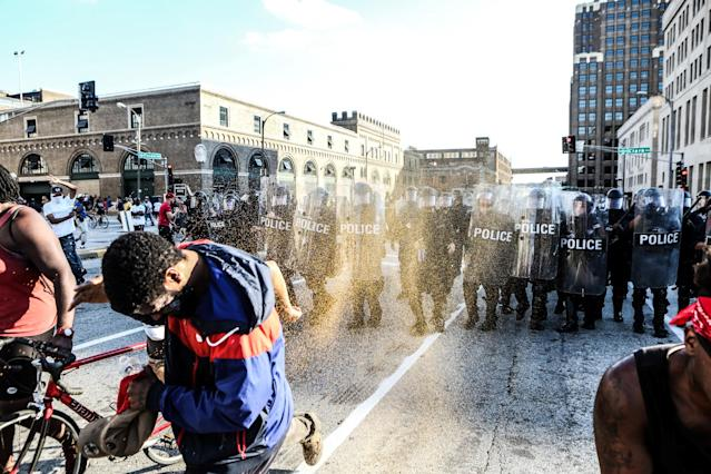 <p>Protesters shield themselves from pepper spray by police in riot gear during a protest after a not guilty verdict in the murder trial of former St. Louis police officer Jason Stockley, charged with the 2011 shooting of Anthony Lamar Smith, who was black, in St. Louis, Mo., Sept. 15, 2017. (Photo: Lawrence Bryant/Reuters) </p>