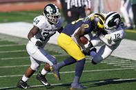 Michigan wide receiver Giles Jackson (0) is pulled out of bounds by Michigan State cornerback Chris Jackson (12) during the second half of an NCAA college football game, Saturday, Oct. 31, 2020, in Ann Arbor, Mich. (AP Photo/Carlos Osorio)