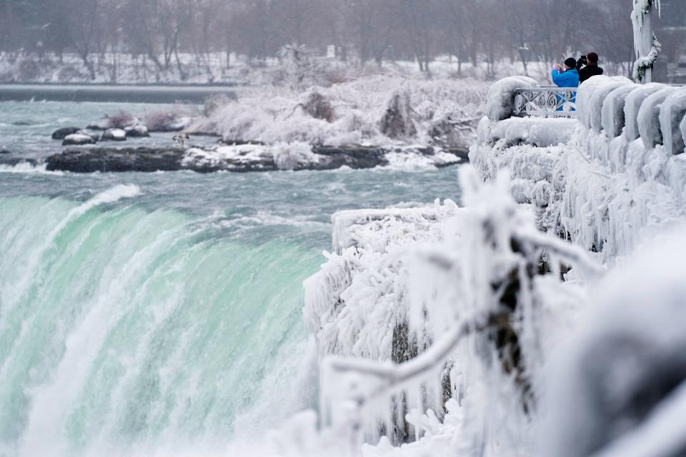 TOPSHOT - Two men take photographs at the Horseshoe Falls in Niagara Falls, Ontario, on January 27, 2021. (Photo by Geoff Robins / AFP) (Photo by GEOFF ROBINS/AFP via Getty Images)