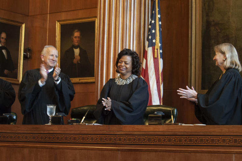 """FILE - In this March 7, 2019  file photo, Associate Justices Paul Newby and Robin Hudson applaud for new Chief Justice Cheri Beasley, center, of the N.C. Supreme Court during Beasley's investiture ceremony in Raleigh. In North Carolina's Supreme Court chamber, above the seat held by Beasley, the second African American chief justice, hangs a towering painting of Chief Justice Thomas Ruffin, a 19th century slave owner and jurist who authored a notorious opinion about the """"absolute"""" rights of slaveholders over the enslaved.In October 2018 the state Supreme Court named a commission to review the portraits in the building that houses the court ,including Ruffin's. (Paul Woolverton/The Fayetteville Observer via AP)"""