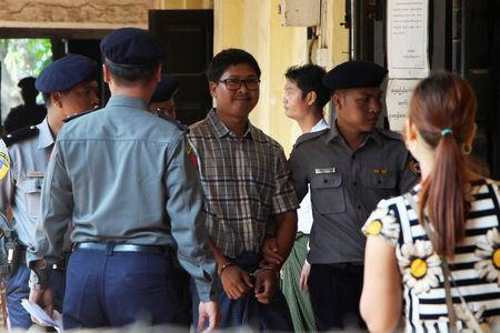 Detained Reuters journalist Wa Lone is escorted by police as he arrives at a court hearing in Yangon, Myanmar March 14, 2018. REUTERS/Stringer