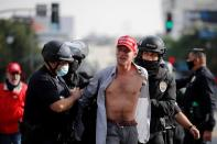A supporter of U.S. President Donald Trump wearing a Make America Great Again (MAGA) hat reacts upon getting detained by the police while protesting in Los Angeles, California