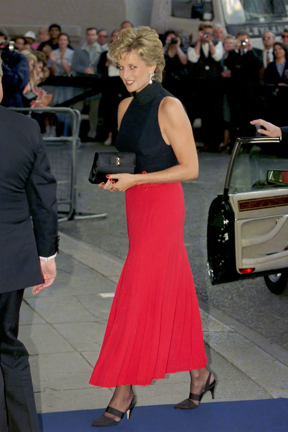 <p>In a red pleated skirt and black high-neck top at a Pavarotti concert in London. </p>