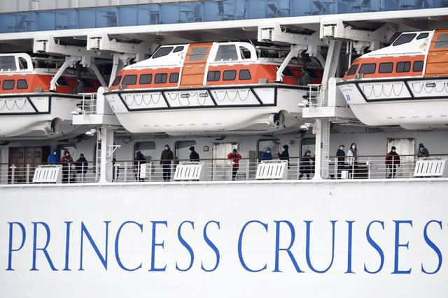 Masked passengers are seen on the deck of the Diamond Princess