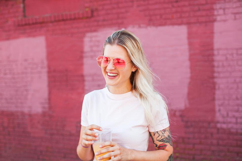 Young blonde woman with tattoos wearing pink sunglasses holding a plastic cup of juice laughing in front of pink wall