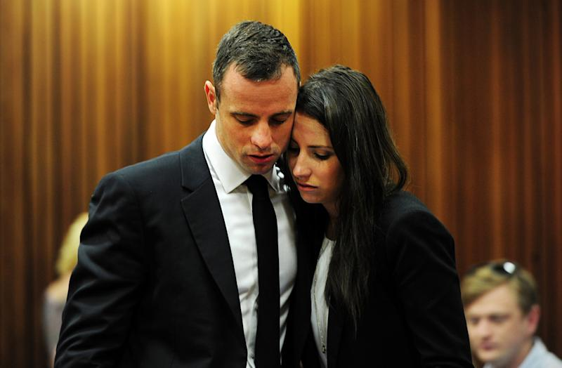 Oscar Pistorius hugs his sister Aimee, right, in court in Pretoria, South Africa, Wednesday, March 19, 2014. Pistorius is on trial for the murder of his girlfriend Reeva Steenkamp on Valentine's Day in 2013. (AP Photo/Leon Sadiki, Pool)