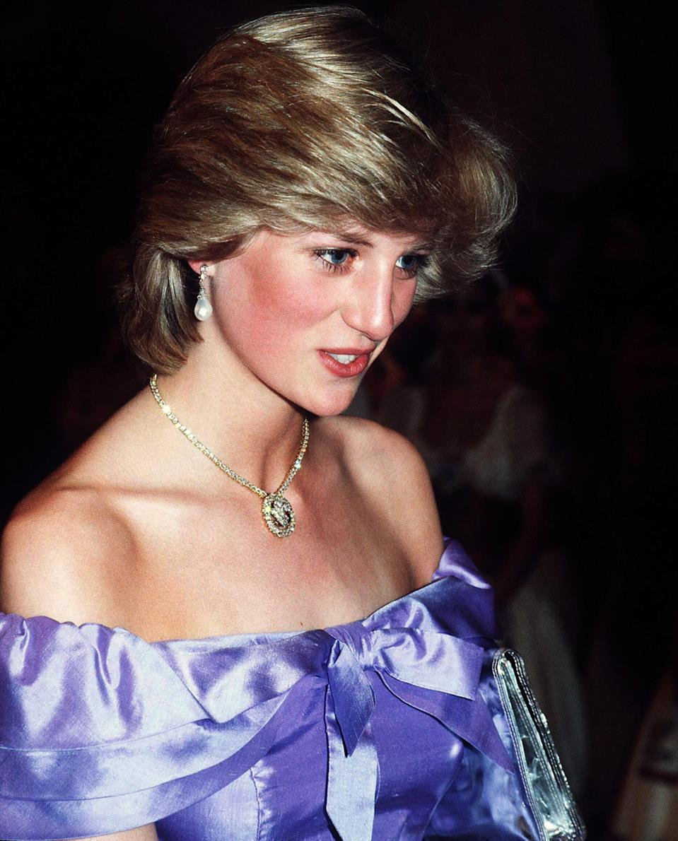 <p>For a theatre performance in the early eighties, Princess Diana opted for a cold-shoulder dress in a striking violet hue. She finished the look with pearl earrings and a feathered bouffant.<br><em>[Photo: PA]</em> </p>