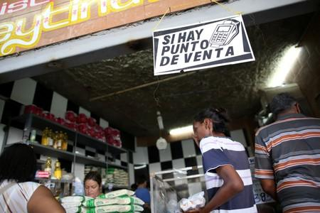 Customers buy products at a store in Caracas