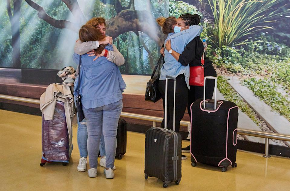 Travellers hug in the arrival terminal of Lisbon's airport during the first day of new, relaxed travel regulations between UK and Portugal (Getty Images)