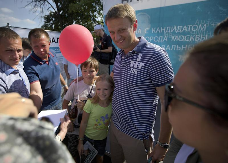 In this photo taken Wednesday, Aug. 21, 2013, Alexei Navalny, center, poses for a photo in downtown Moscow. Alexei Navalny, the anti-corruption blogger and a leader of the Russian protest movement, will face the incumbent Sergei Sobyanin, who has proven an invisible candidate rarely spotted on the debate floor or shaking hands with voters, in the upcoming Moscow's mayor election on Sept. 8. (AP Photo/ Ivan Sekretarev)