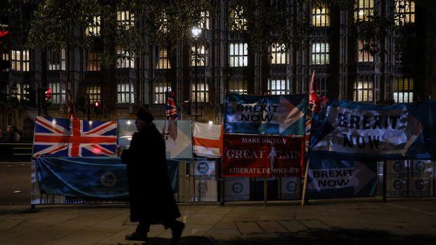 A man walks past banners near the British Houses of Parliament in Westminster as MPs debate the early parliamentary election on October 29, 2019